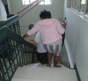 An elderly patient going down stairs at a health service.